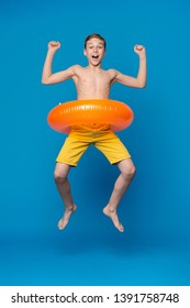 Happy child boy in swimsuit jumping with swimming ring, blue studio background