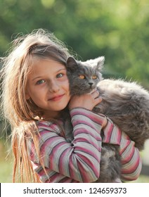 Happy child with cat. Kid showing
