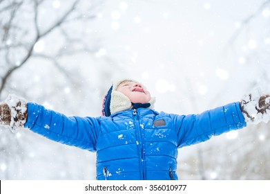 Happy child catches snowflakes mouth in winter park