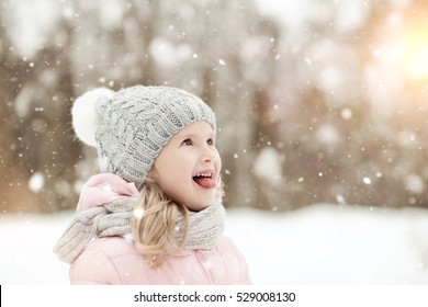 happy child catches snowflakes in winter Park, sticking his tongue out