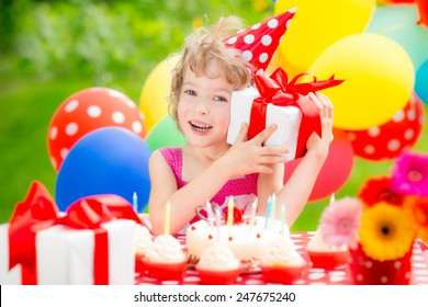 Happy child celebrating birthday. Kid having fun in spring garden