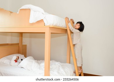 Happy child in child's room on a bunk-beds