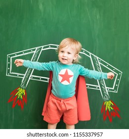 Happy child in class. Funny kid against chalkboard. Back to school. Education concept