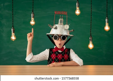 Happy child in classroom. Funny kid with light bulb against green chalkboard background. Innovation technology in education. Bright new idea concept. Back to school