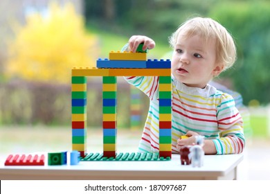 Happy child, cute blonde toddler girl building house from plastic blocks sitting next to a big window indoors at home or kindergarten