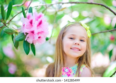 Happy child cute girl smile in gorgeous garden with flower magnolia