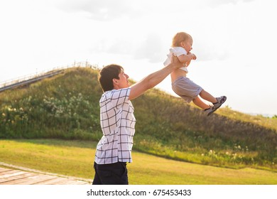 Happy child, dad and son having fun, holding on hands on a sunlight sunset background. Family, travel, vacation, childhood, father's day - concept