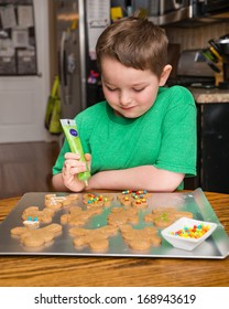 Happy child decorating ginger bread man cookie