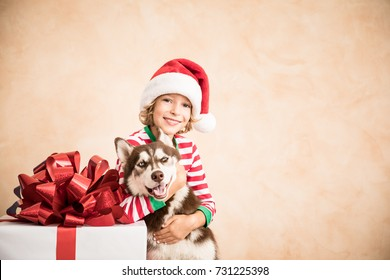 Happy child and dog on Christmas eve. Kid and pet dressed in Santa Claus hat. Child having fun with husky at home. Chinese calendar new year concept