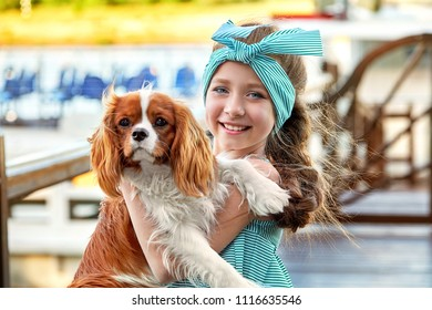 Happy child with dog. Portrait close-up joy face girl hugs puppy breed cocker spaniel, cavalier charles king. Charming cute pet, dog, animal, friendship with kid.