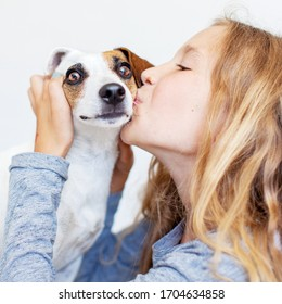 Happy child with dog. Portrait girl with pet. Teen kissing Jack Rassell
