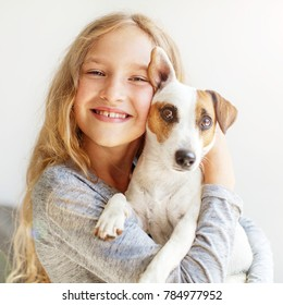 Happy child with dog. Portrait girl with pet. Jack Rassell with teen embracing
