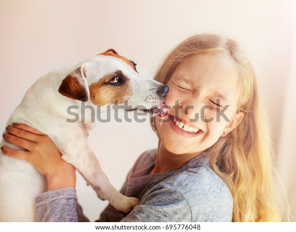 Joyeux enfant avec chien. Portrait de fille avec animal de compagnie. Jack Russell lèche un adolescent