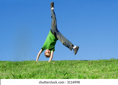 happy child doing cartwheel on hill