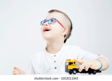 Happy child with down syndrome playing with toy truck.