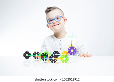 Happy child with down syndrome playing with building toys.