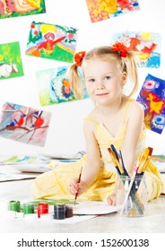 Happy child drawing with brush in album. Creativity concept.