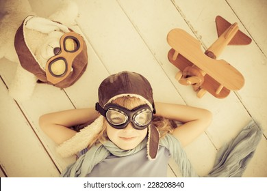 Happy child dressed in pilot hat and glasses. Kid playing with toy airplane and teddy bear at home. Dream and freedom concept. Retro toned