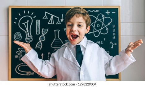 Happy child dressed as a scientist in front of chalkboard with drawings