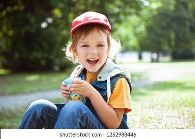 Happy child drinking juice out of a box on the street.