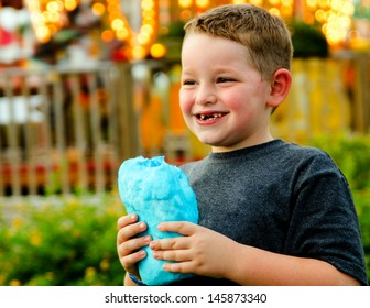 Happy child eating cotton candy at carnival