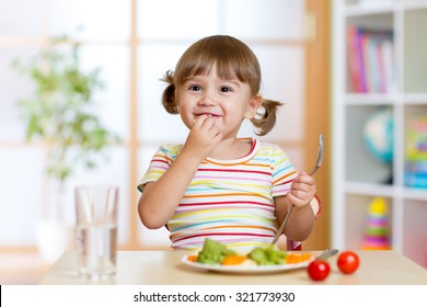 Happy child eats vegetables sitting at table in nursery