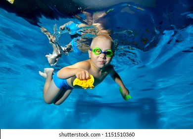 Happy child engaged in sports swimming in the pool. He swims underwater on a blue background in swimming goggles and with toys in his hands. Portrait. Underwater photography.