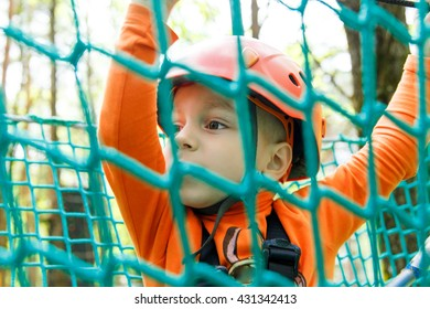 Happy child enjoying in a climbing adventure park on a summer day