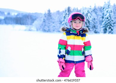 Happy child enjoying vacation in Alpine resort. Little girl skiing in mountains. Active sportive toddler wearing helmet and glasses learning to ski. Winter sport for family. Skier racing in snow.