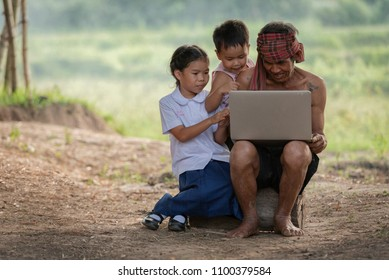 Happy child and father use outdoor laptop