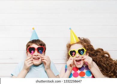Happy child friend in carnival party, lying on a wooden floor. Happy childhood, holiday 2020 concept. High top view.