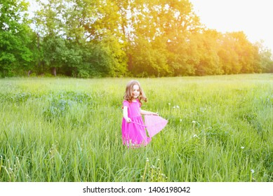 Happy child girl 4 years catches butterflies with a pink nipple on a Sunny summer day. Holidays and children's rest concept.