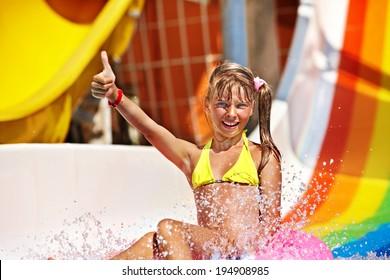 Happy child girl in bikini sliding water park.