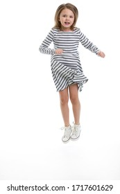 Happy child girl in casual dress playing and jumping isolated on white background. Cute little blond girl looking at camera.