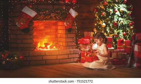 happy   child girl with christmas gift at evening home