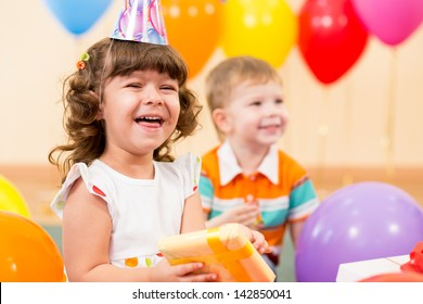 happy child girl with colorful balloons and gift