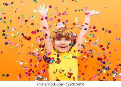 happy child girl with confetti on orange background. Holidays. Birthday