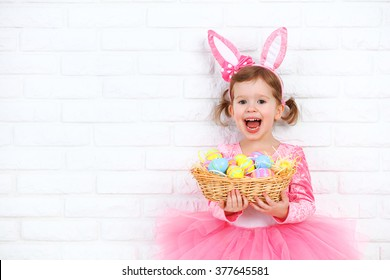 Happy child girl in a costume Easter bunny rabbit with ears and a basket of eggs
