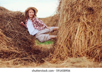happy child girl in country style plaid shirt and hat relaxing on summer field with hay stacks