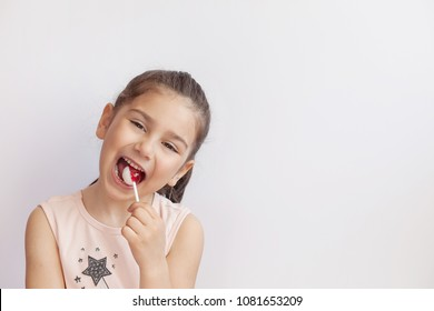 Happy child girl eating candy lollipops.
