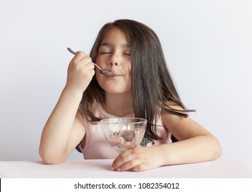 Happy child girl eating ice cream in white and chocolate bowl on white background. Enjoying delicious.