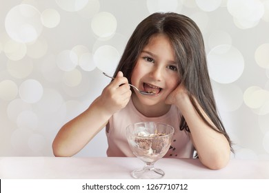 Happy child girl eating ice cream in white and chocolate bowl on light background. Enjoying delicious. Delicious food.