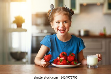 happy child girl eating strawberries with milk at home