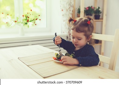 the happy child girl  eating vegetables