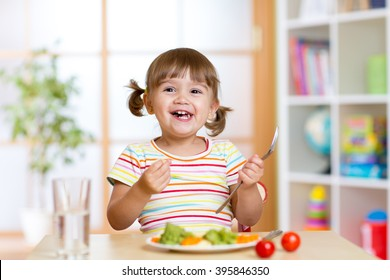 Happy child girl eating vegetables. Healthy nutrition for kids