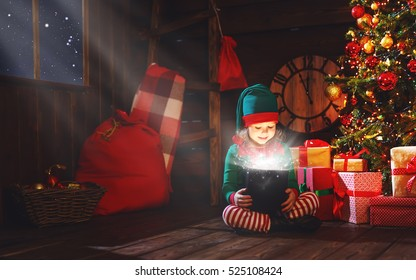happy child girl elf helper of Santa with a magic Christmas gift