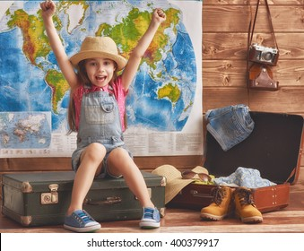 Happy child girl getting ready for the journey. Girl packs her bags and having fun.