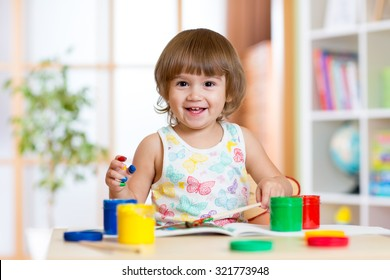 Happy child girl with hands painted color paints at home