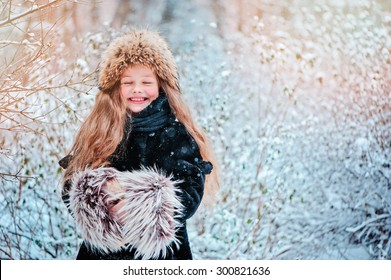 happy child girl having fun on the walk in winter snowy forest in fur hat