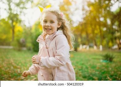 Happy child girl having fun in autumn park